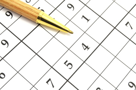 closeup of an unfinished sudoku puzzle with brown pen photo