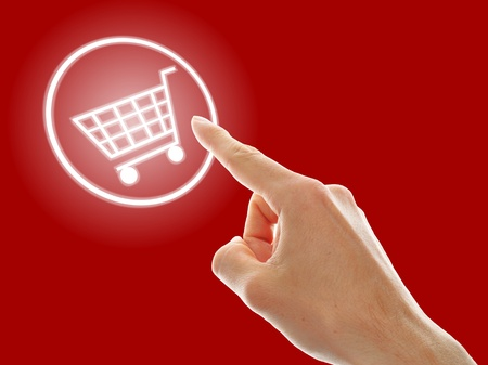 shopping cart button presses by a male hand on red background photo