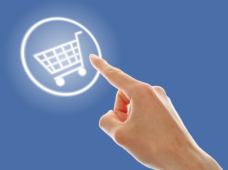 shopping cart button presses by a male hand on blue background Stock Photo - 13238633