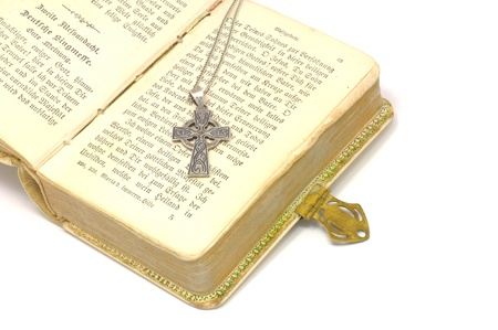 silver cross on bible isolated on white background Stock Photo - 13634627