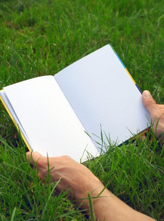 A blank opened book outdoors lying on the green grass  photo