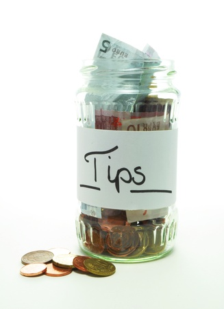 tip jar with bills and coins on white background Stock Photo - 13634604
