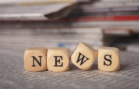 reading news: the word news on cubes on a newspaper Stock Photo