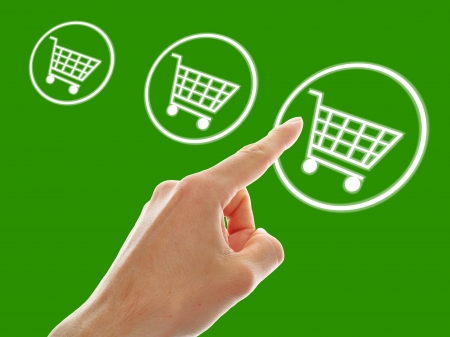 shopping cart button presses by a male hand on green background Stock Photo - 13952551
