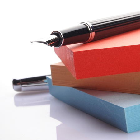 pen on a stack of colored notes on white background Stock Photo - 13952545