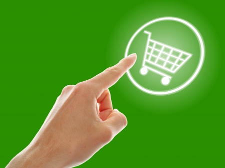 shopping cart button presses by a male hand on green background photo