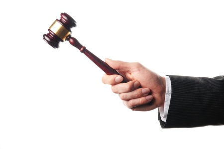 commercial law: an auctioneers hand is holding a wooden gavel Stock Photo