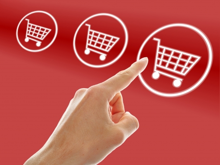 shopping cart button presses by a male hand on red background Stock Photo - 15541873