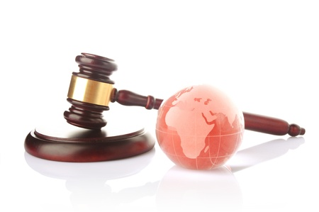 a colored globe with brown gavel on white background photo