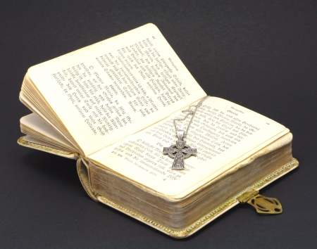 silver cross on bible isolated on black background photo