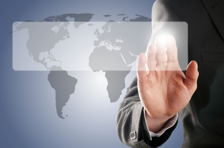 businessman pressing one touchscreen button in front of the worldmap photo