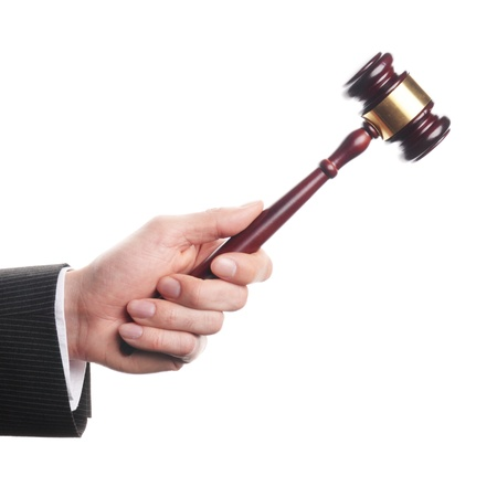 an auctioneers hand is holding a wooden gavel photo