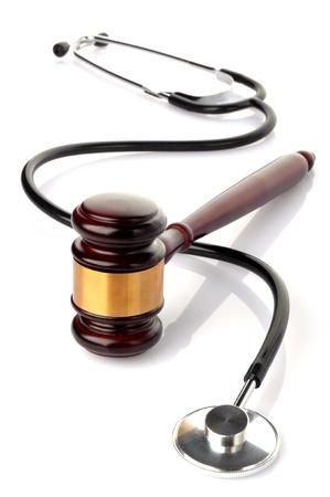 autoridad: concepto sobre la demanda médica, stethoscpe y martillo en fondo blanco Foto de archivo