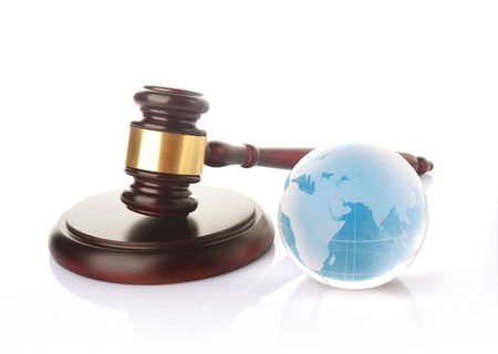 a colored globe with brown gavel on white background Standard-Bild