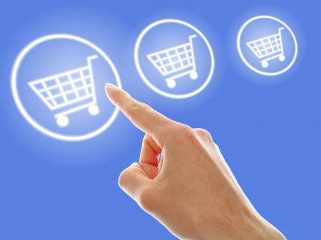 shopping cart button presses by a male hand on blue background Stock Photo - 16667654
