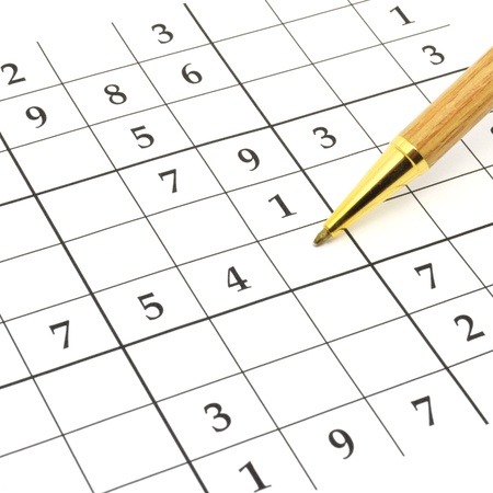crossword puzzle: closeup of an unfinished sudoku puzzle with brown pen