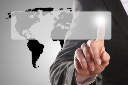 worldmap: businessman pressing one touchscreen button in front of the worldmap Stock Photo