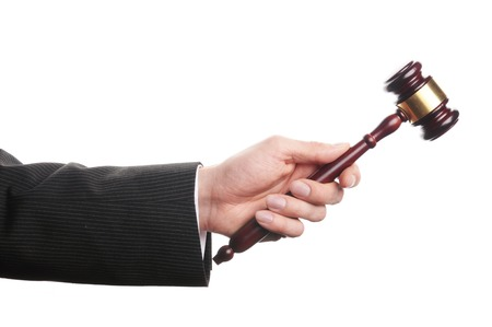 auctioneer: an auctioneers hand is holding a wooden gavel Stock Photo