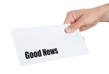 delievery: hand giving an envelope with Good News on it Stock Photo