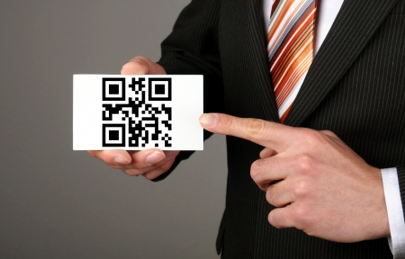 businessman holding a card with qr code which means contact us photo
