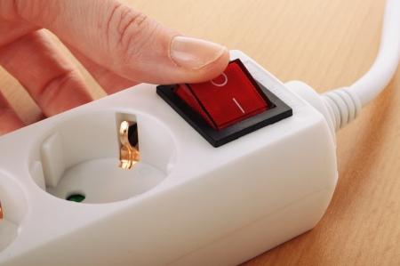 socket: someone power on the white multiple socket outlet Stock Photo