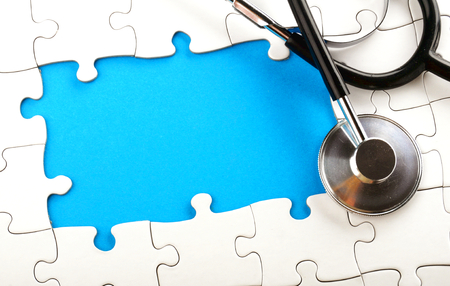 strategically: a stethoscope lying on an unfished puzzle