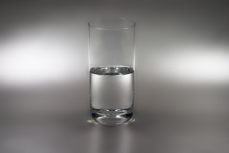 half leeg (of half vol) glas water Stockfoto