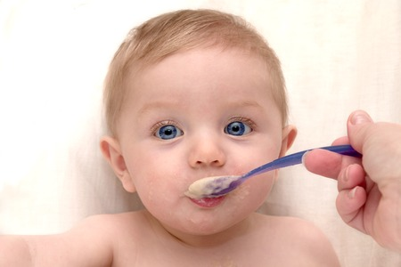 Baby boy being fed oatmeal Stock Photo