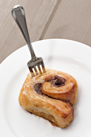 tantalizing: Cinnamon roll with fork Stock Photo