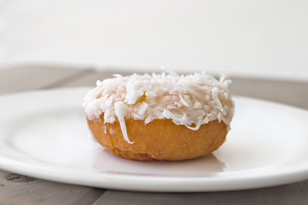 tantalizing: Single coconut-covered donut on white plate