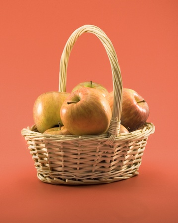 Basket full of apples on a red background photo