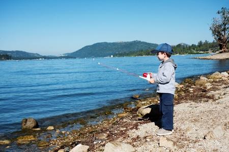 Small boy fishing on lake