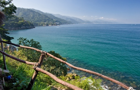 Tropical Puerto Vallarta, Mexico from shore behind a rustic wooden fence Stock Photo
