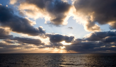 peaking: Cloudy sunset with sun rays peaking through