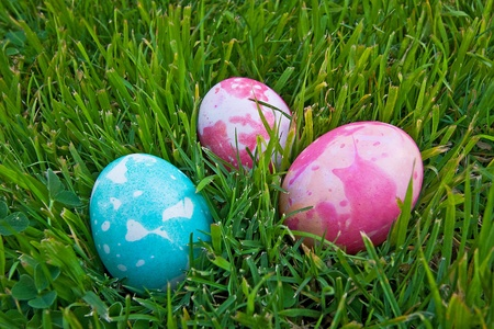 Three colorful Easter eggs laying in the grass