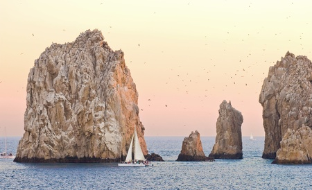 Sailing in a yellow and orange sunset around Los Arcos in Cabo San Lucas, Mexico