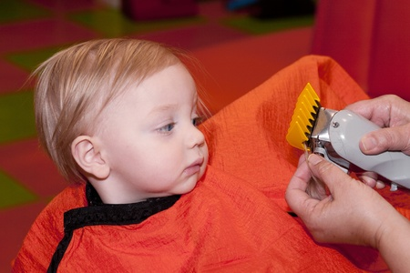 haircut: Baby boy looking at clippers as he gets his first haircut at a barber shop Stock Photo