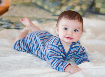 Baby lying on bed posing for picture wearing blue striped outfit photo