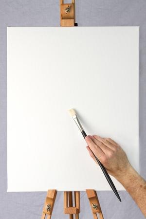 Close-up artysty począwszy do malowania na pustym płótnie na sztaludze, gotowy do dodawania własnych obraz lub tekst lub projekt