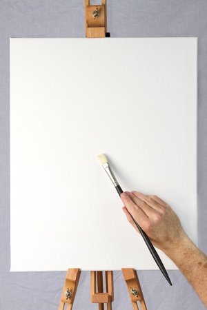 Close-up of artist starting to paint on a blank canvas on an easel, ready for adding your own image or text or design