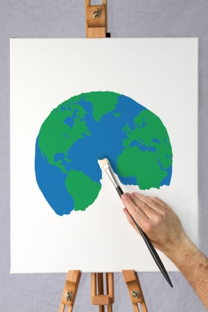 Close-up of artist painting a picture of the world on a canvas attached to an easel