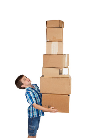 Young boy struggling with a tower of cardboard boxes isolated on white background Stock Photo
