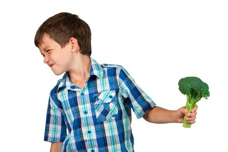 desprecio: El muchacho joven que gira la cabeza con disgusto lejos de un Manojo del bróculi