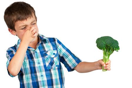 desprecio: Niño pequeño que mira fijamente un manojo de brócoli con disgusto