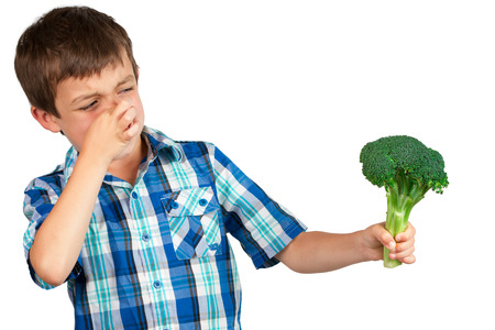 Small boy staring at a bunch of broccoli with disgust photo
