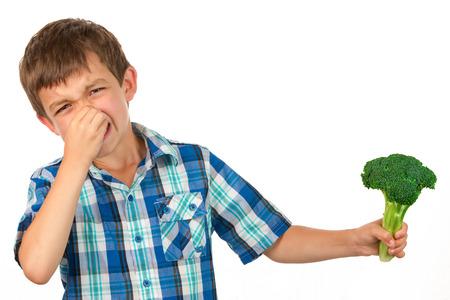 desprecio: Pequeño niño sosteniendo un ramo de brócoli y tiene una mirada de disgusto en su cara Foto de archivo