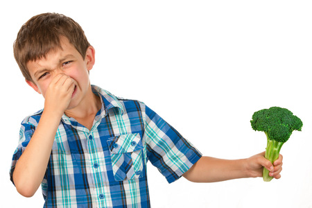 Small Boy Holding a Bunch of Broccoli and has a disgusted look on his face Stock Photo