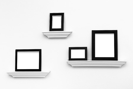 Multiple black and white picture frames on picture ledges attached to a white wall - ready for your custom images to insert