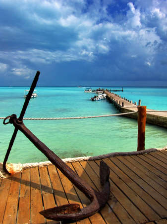 Caribbean Seascape with blue sky, turquoise water and old anchor