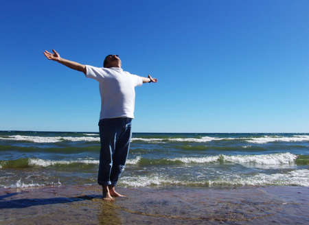 Man with  arms outstretched standing on the lakeshore and  looking up